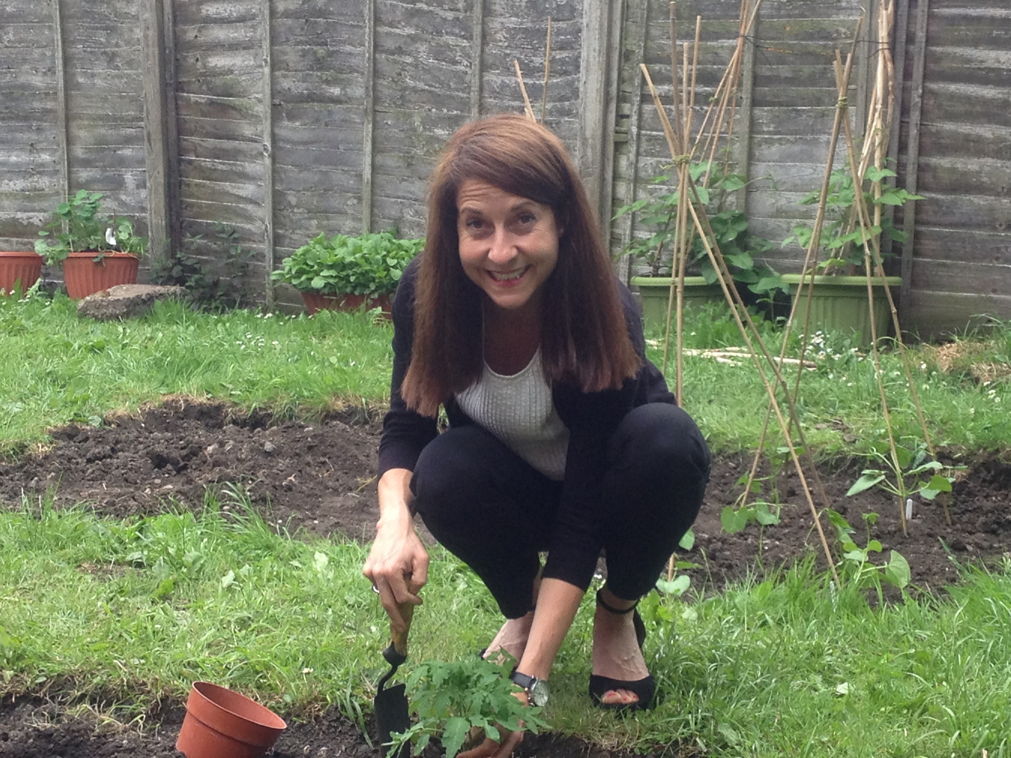 Liz planting tomatoes at Beaumont Lodge Garden Project